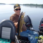 man in hat holding up walleye he caught